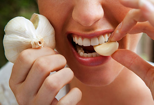 getty_rm_photo_of_woman_biting_into_raw_garlic_clove